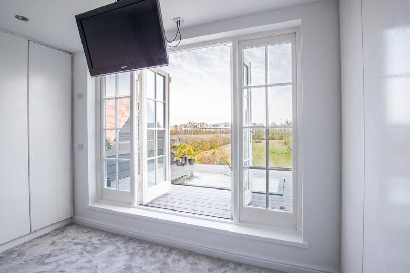 Steel framed glass extension, bedroom Hertfordshire by Aubrey Homes